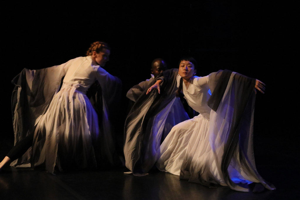 Three people, white robes, dance