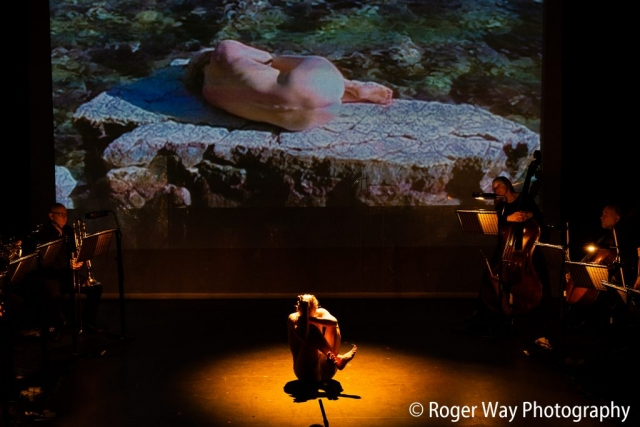 A naked performer sits in a foetal position on an empty stage.