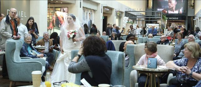 A woman in a wedding dress passes through a café.
