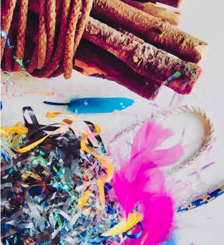 Various sticks, ropes, feathers, and bits of glitter on a white background.