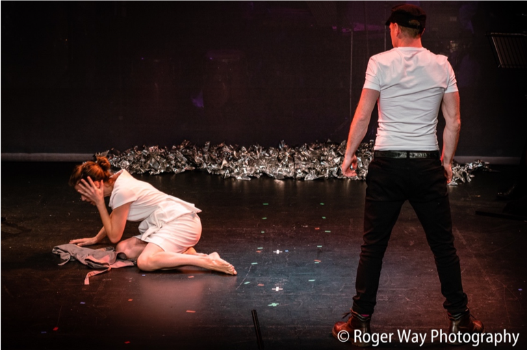 Two performers; one kneeling with a hand to her face, another standing in an aggressive posture