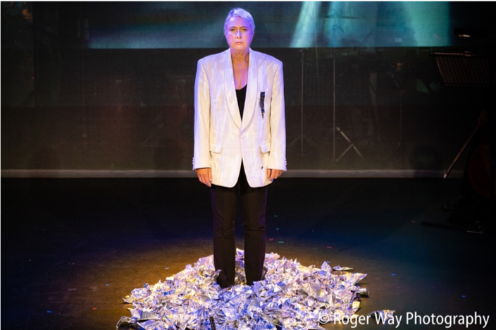 A woman in a white suit jacket stands in the middle of a stage